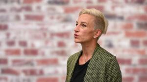 Claudia Tölle steht vor einer Ziegelsteinmauer