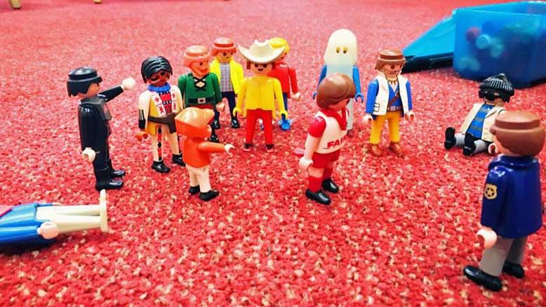 Mehr als 10 Playmobil-Männchen stehen oder sitzen aufgereiht zusammen - Symbolbild