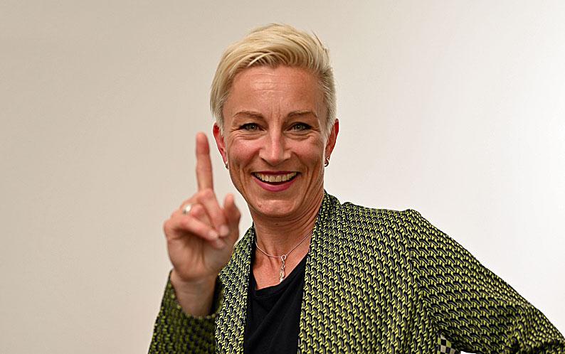 Claudia Tölle zeigt mit dem Zeigefinger und lächelt dabei in die Kamera