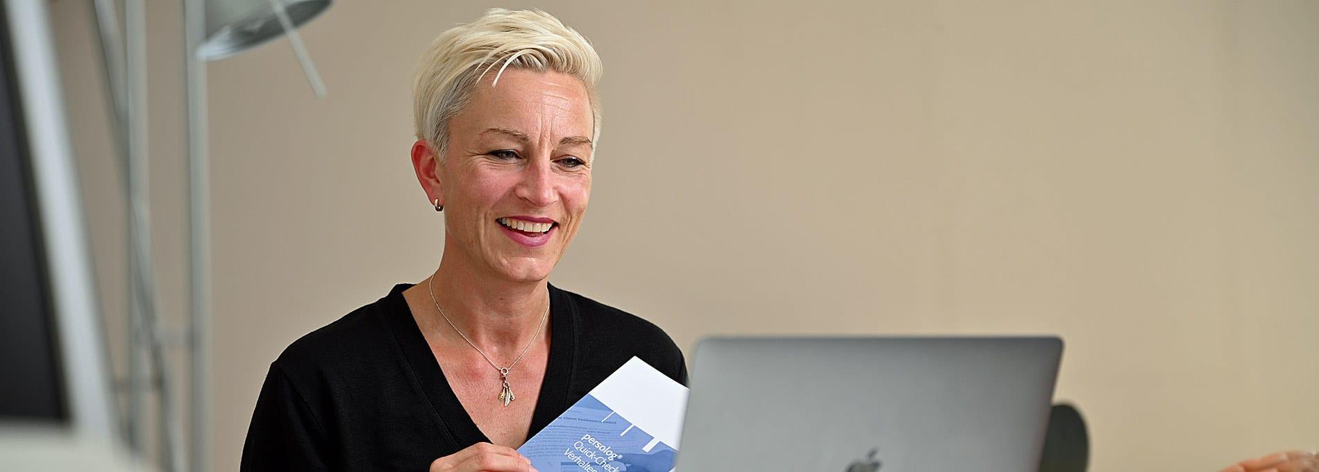Claudia Tölle hält einen Flyer von Persolog in der Hand