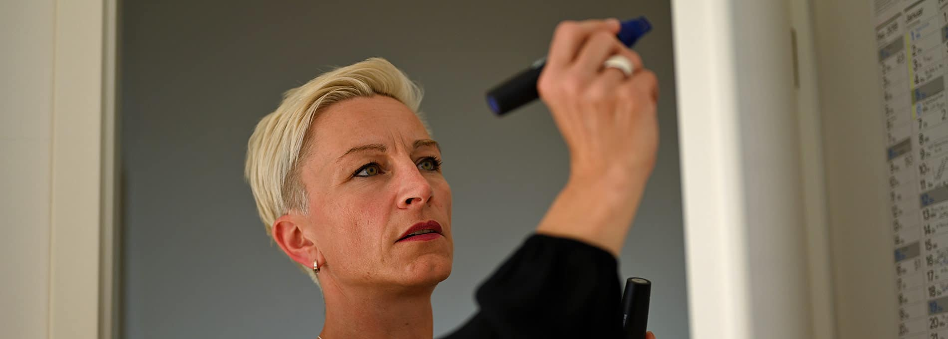 Claudia Tölle schreibt mit einem dicken Filzmaler auf ein Flipchart